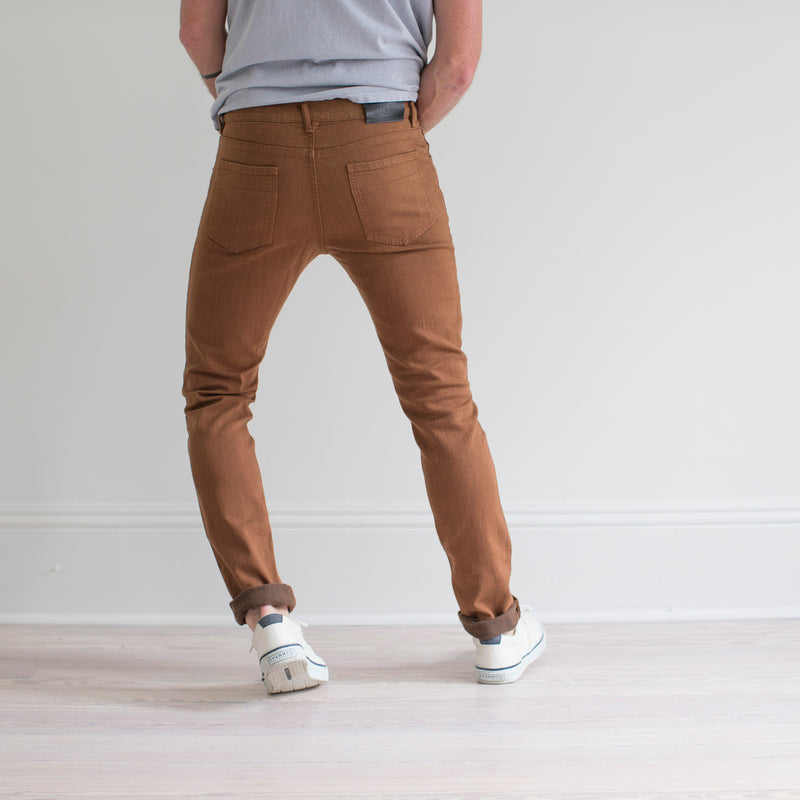 angle: whiskey  A model wears Raleigh Denim Workshop Martin fit stretch pants in brown, back view