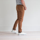 angle: whiskey  A model wears Raleigh Denim Workshop Martin fit stretch pants in brown, side view
