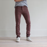 angle hover: russet  A model wears Raleigh Denim Workshop Martin fit stretch pants in maroon, side view