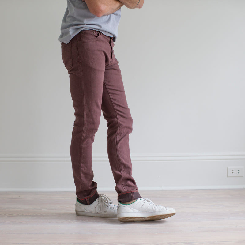 angle: russet  A model wears Raleigh Denim Workshop Martin fit stretch pants in maroon, side view