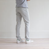 angle: mercury  A model wears Raleigh Denim Workshop Martin fit stretch pants in white, back view