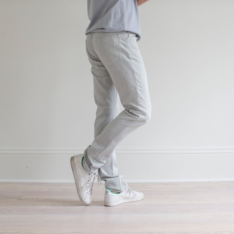 angle hover: mercury  A model wears Raleigh Denim Workshop Martin fit stretch pants in white, side view