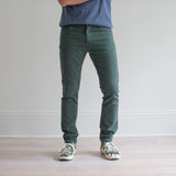 angle: hemlock  A model wears Raleigh Denim Workshop Martin fit stretch pants in green, front view