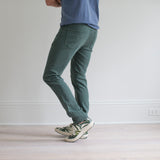 angle: hemlock  A model wears Raleigh Denim Workshop Martin fit stretch pants in green, side view