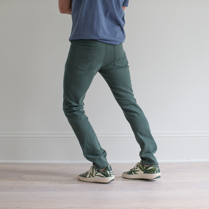 angle hover: hemlock  A model wears Raleigh Denim Workshop Martin fit stretch pants in green, side view