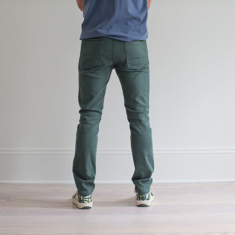 angle: hemlock  A model wears Raleigh Denim Workshop Martin fit stretch pants in green, back view