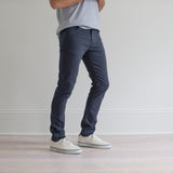 angle hover: iron blue  A model wears Raleigh Denim Workshop Martin fit stretch pants in blue, side view