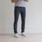 angle: iron blue  A model wears Raleigh Denim Workshop Martin fit stretch pants in blue, front view