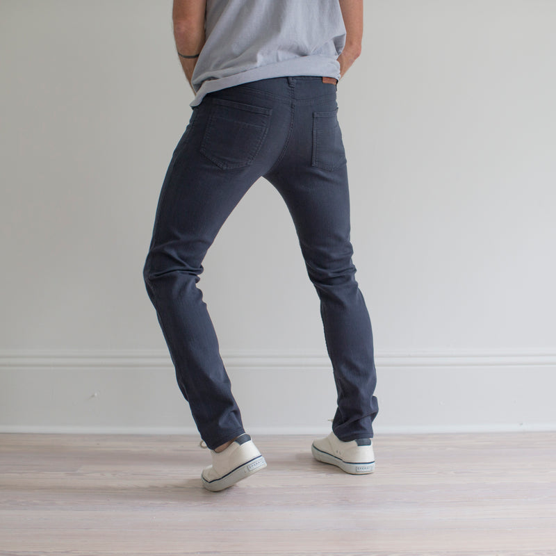 angle: iron blue  A model wears Raleigh Denim Workshop Martin fit stretch pants in blue, back view