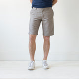 angle hover: flax  A model wears Raleigh Denim Workshop Jones thin fit shorts in tan (flax), front view
