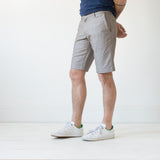 angle: flax  A model wears Raleigh Denim Workshop Jones thin fit shorts in tan (flax), front view