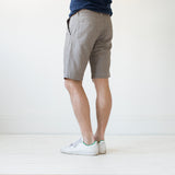angle: flax  A model wears Raleigh Denim Workshop Jones thin fit shorts in tan (flax), back view