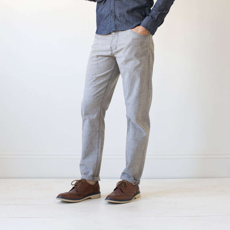 angle hover: skyline  A model wears Raleigh Denim Workshop Graham work taper fit jeans that are in light gray, front view