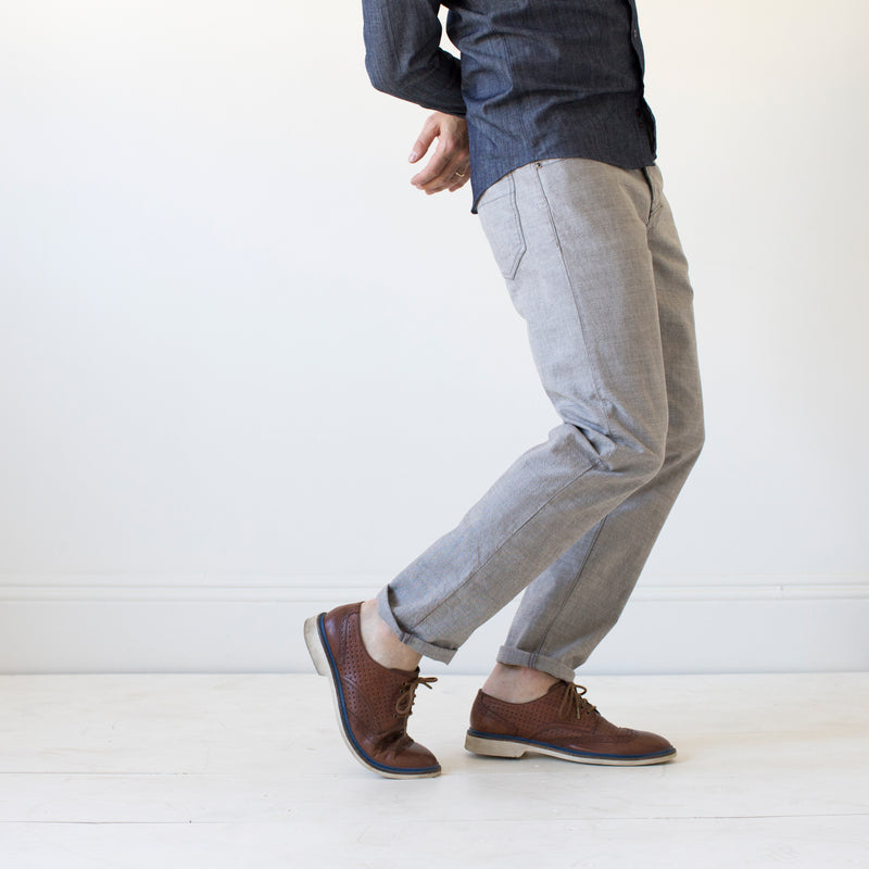 angle: skyline  A model wears Raleigh Denim Workshop Graham work taper fit jeans that are in light gray, front view