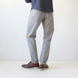 angle: skyline  A model wears Raleigh Denim Workshop Graham work taper fit jeans that are in light gray, back view