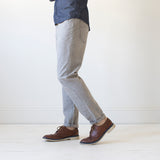 angle: skyline  A model wears Raleigh Denim Workshop Graham work taper fit jeans that are in light gray, side view