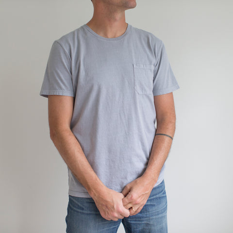 angle: grey | A model wears Raleigh Denim Workshop cotton pocket crew neck tee in gray, front view