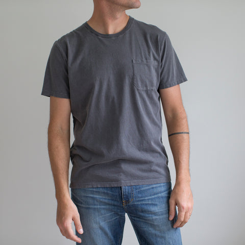 angle: charcoal | A model wears Raleigh Denim Workshop cotton pocket crew neck tee in charcoal, front view