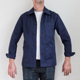 angle: navy polo  A model wears Raleigh Denim Workshop chore coat in navy, front view
