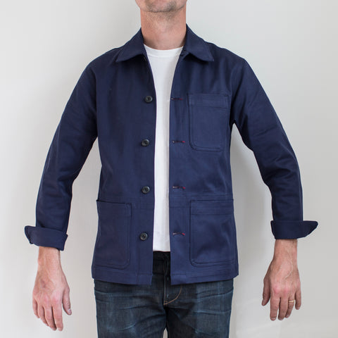 angle: navy polo | A model wears Raleigh Denim Workshop chore coat in navy, front view