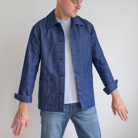 angle: indigo | A model wears Raleigh Denim Workshop chore coat in blue, front view