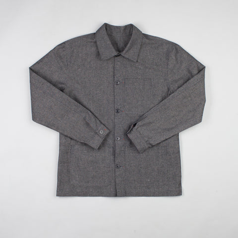 angle: basalt | A model wears Raleigh Denim Workshop chore coat in gray, front view