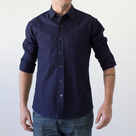 angle: indigo seer | Model wears a Raleigh Denim Workshop men's welt-pocket button-up shirt in navy indigo seer.