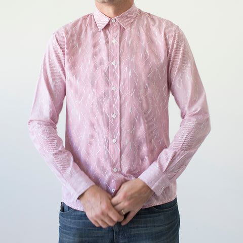 angle: voltage | A model wears Raleigh Denim Workshop men's classic button-up shirt in red/pink voltage.