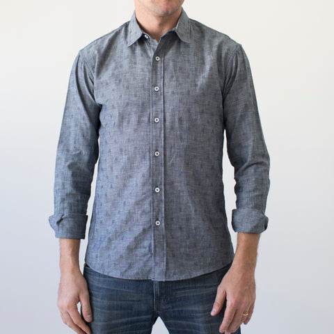 angle: crosshatch | A model wears Raleigh Denim Workshop blue crosshatch men's classic button-up shirt, front view