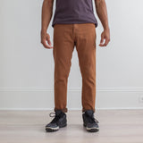 angle: cedar  Raleigh Denim Workshop a model wears Martin thin taper fit stretch pants in brown-orange cedar, front