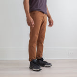 angle: cedar  Raleigh Denim Workshop a model wears Martin thin taper fit stretch pants in brown-orange cedar, side