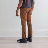 angle: cedar  Raleigh Denim Workshop a model wears Martin thin taper fit stretch pants in brown-orange cedar, back