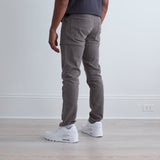 angle: stainless  Raleigh Denim Workshop a model wears Martin thin taper fit stretch pants in grey stainless, back