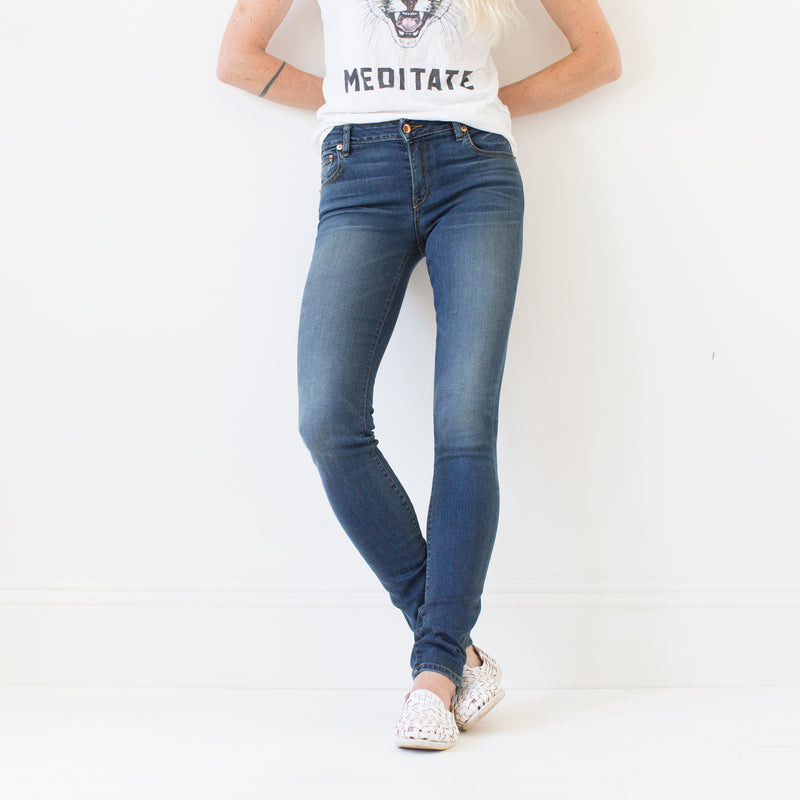 angle hover: vintage  A model wears Raleigh Denim Workshop Surry mid-rise thin fit vintage wash jeans, front view