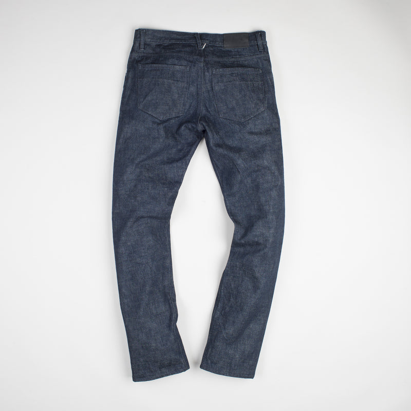 angle: static rinse  Raleigh Denim Workshop men's Jones thin fit selvage raw denim jeans in static dark rinse, back flat view