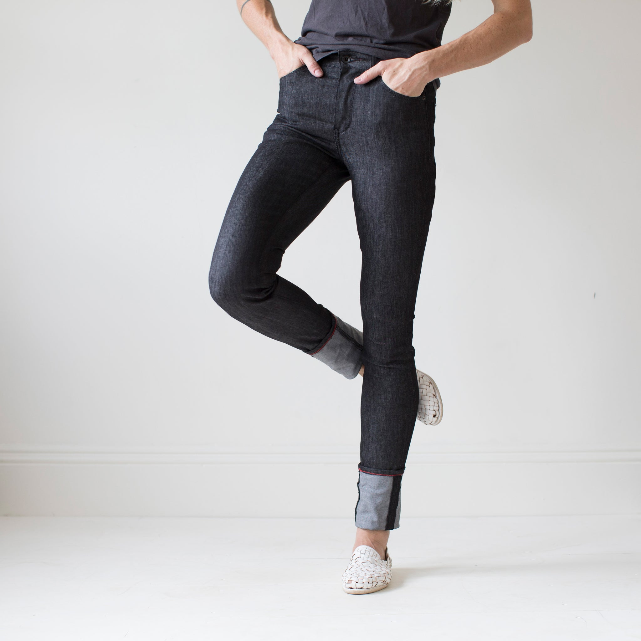 angle hover: black  A model wears Raleigh Denim Workshop Haywood high-rise skinny jeans in black, side view