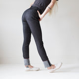 angle: black  A model wears Raleigh Denim Workshop Haywood high-rise skinny jeans in black, back side view
