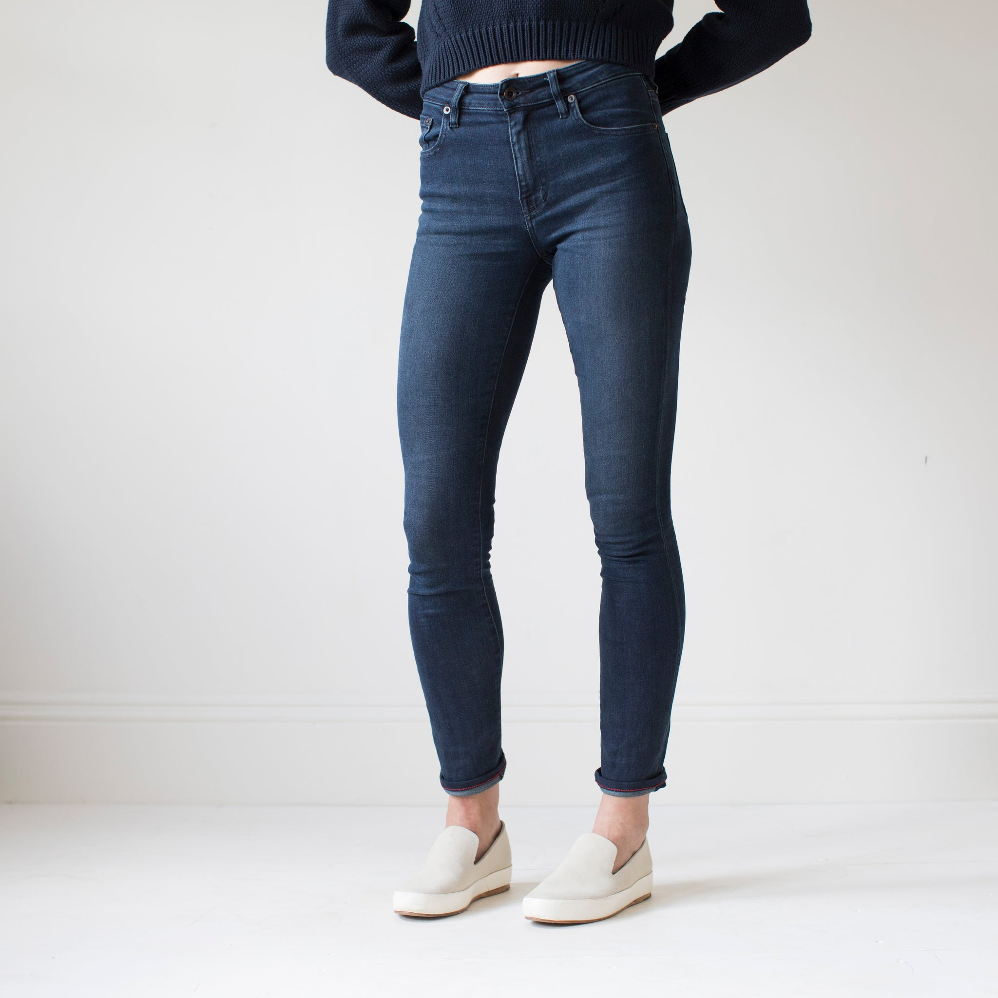 angle hover: canon  A model wears Raleigh Denim Workshop Haywood high-rise skinny jeans with a dark wash, side view