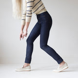 angle: indigo  A model wears Raleigh Denim Workshop Haywood high-rise skinny jeans in dark blue, side view