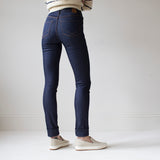 angle: indigo  A model wears Raleigh Denim Workshop Haywood high-rise skinny jeans in dark blue, back view