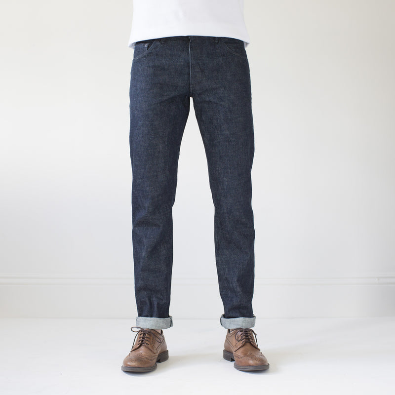 angle hover: static rinse  A model wears Raleigh Denim Workshop men's Jones thin fit selvage raw denim jeans in static dark rinse, front view