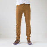angle hover: chestnut  A model wears Raleigh Denim Workshop Martin thin taper fit stretch pants in orange chestnut, front view.