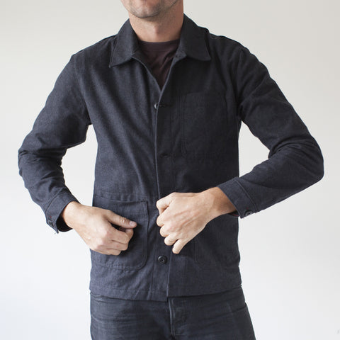 angle: charcoal | A model wears Raleigh Denim Workshop men's chore coat in grey, front view