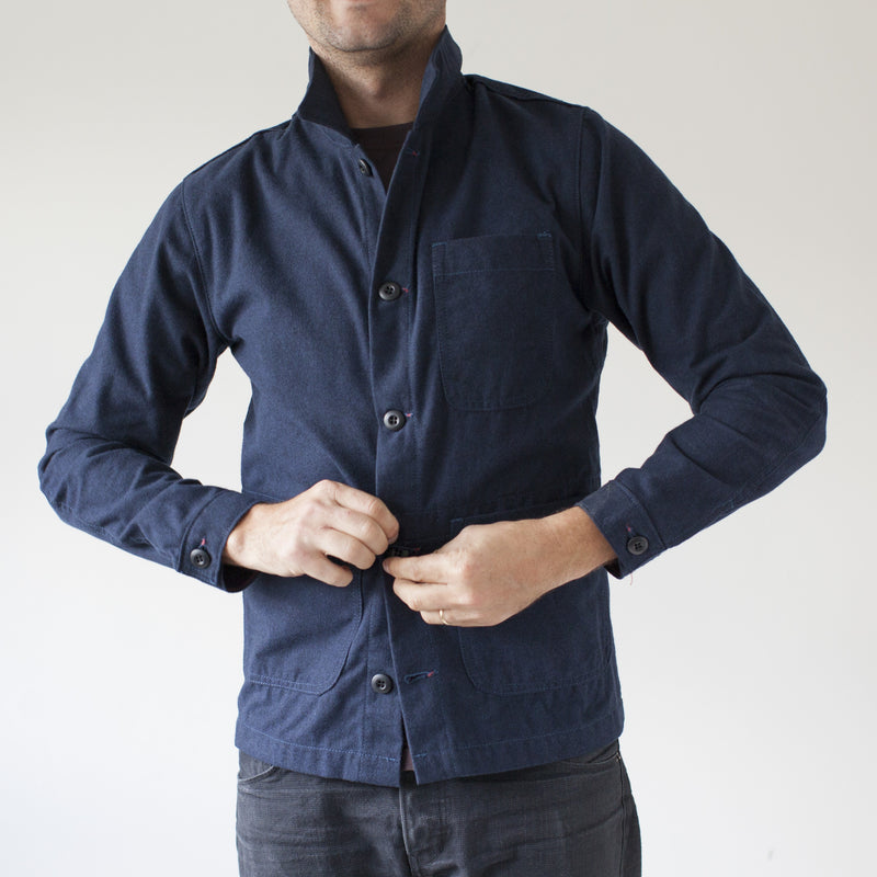 angle: navy  A model wears Raleigh Denim Workshop men's chore coat in navy blue, front view