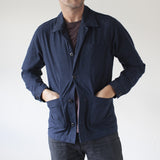 angle hover: navy  A model wears Raleigh Denim Workshop men's chore coat in navy blue, front view