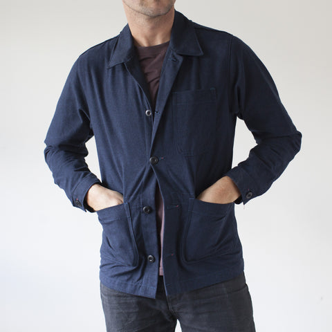 angle: navy | A model wears Raleigh Denim Workshop men's chore coat in navy blue, front view