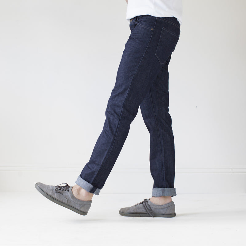 angle: resin rinse  A model wears Raleigh Denim Workshop Jones thin fit in a dark wash, side view