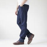angle: resin rinse  A model wears Raleigh Denim Workshop Alexander work fit jeans with a dark wash, side view
