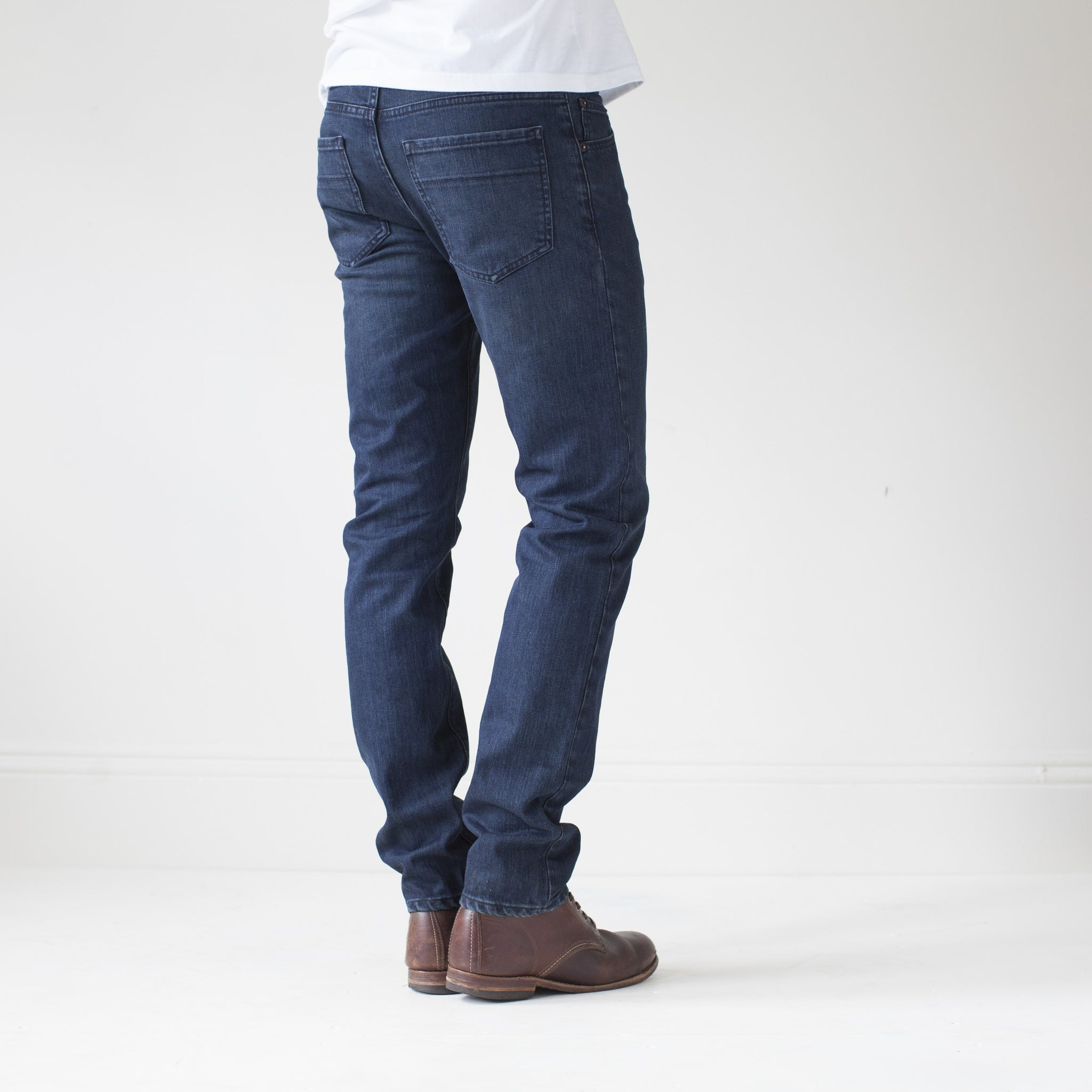 angle: canon  A model wears Raleigh Denim Workshop Martin thin taper fit jeans in original wash, back view