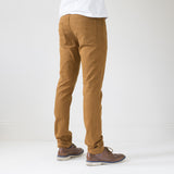 angle: chestnut  A model wears Raleigh Denim Workshop Martin thin taper fit stretch pants in orange chestnut, back view.